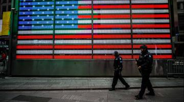 Police officers walking in front of U.S. flag