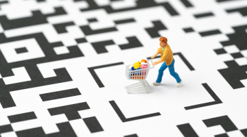 figure of a shopper pushing a cart over a QR code