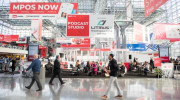 Conference attendees walk past banners at New York's Javits Center