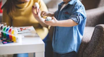 a mom and a little boy are shown painting an easter egg together in the living roome