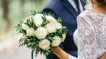 Wedding couple with bouquet of white roses