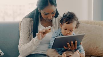 Woman shops on tablet holding a baby