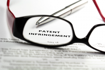 patent infringement paperwork with glasses and pen