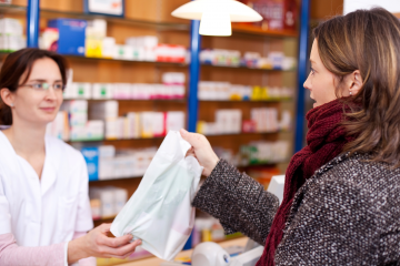 pharmacist handing a bagged prescription to a customer