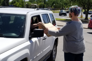 Store employee hands curbside pickup purchases through car window