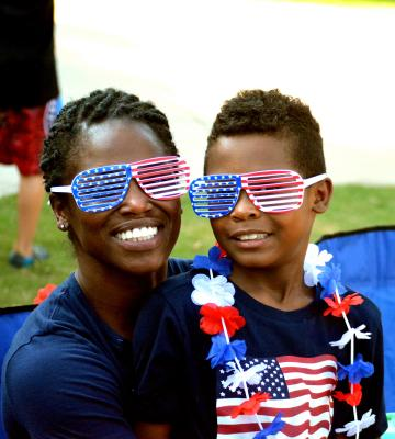 A son sits on his mom's lap for the Independence day celebration