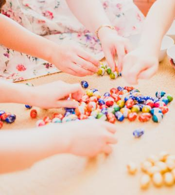 A group of children have their hands in easter candy on the floor