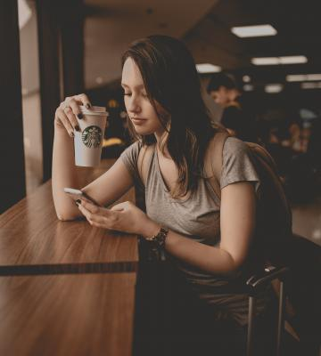 Woman on phone drinking Starbucks coffee at coffeeshop
