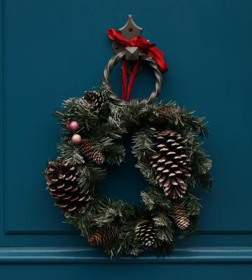 A blue door with a holiday wreath hanging