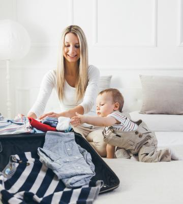 mom and child pack for a vacation in the bedroom