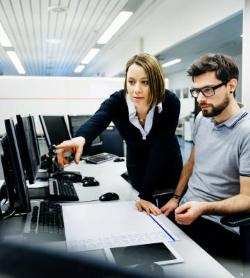 Professional woman pointing at computer for colleague