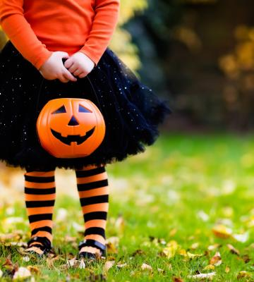 Little girl in Halloween costume and candy bucket playing in park