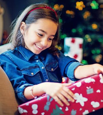 Happy girl opens gift by Christmas tree