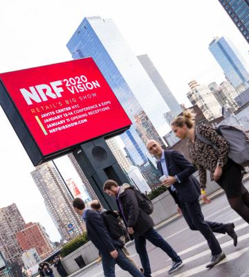 People enter NRF 2020 with sign in background
