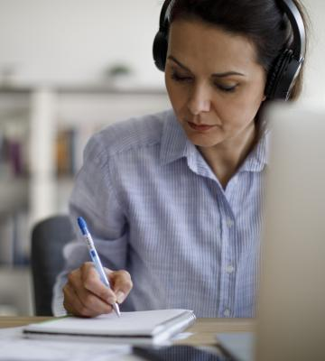 Woman wearing headphones in front of computer takes notes