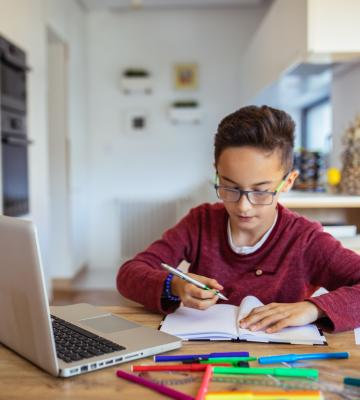 A boy works on schoolwork at laptop
