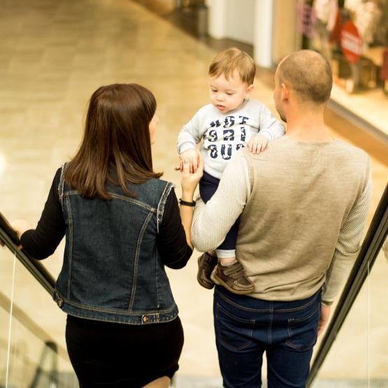 A family going down an escalator with their child at a mall