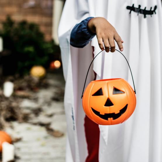 a kid in their halloween costume stands with his halloween pumpkin for trick or treating