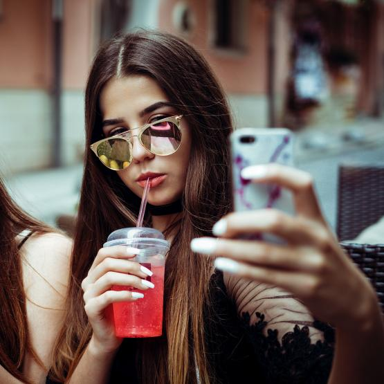 Teenage girls with drinks taking a selfie