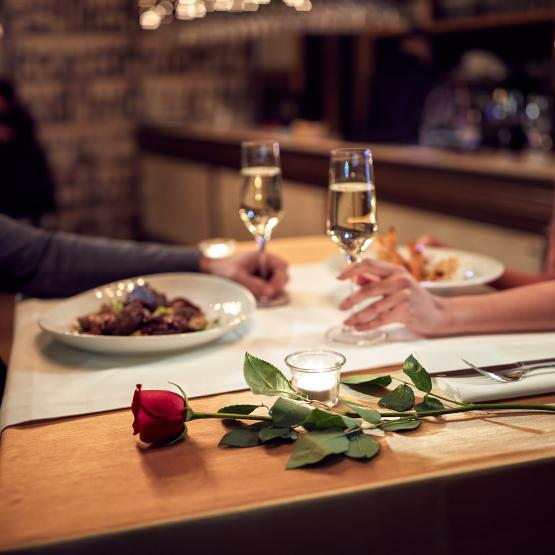 Couple on a romantic dinner date together with wine and food