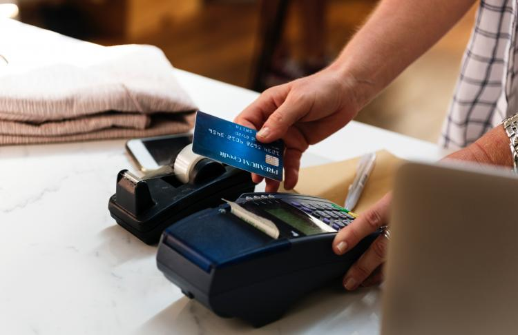 Cashier swiping credit card on a portable machine