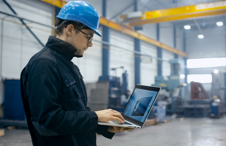 manufacturer worker checking engineering file on a laptop