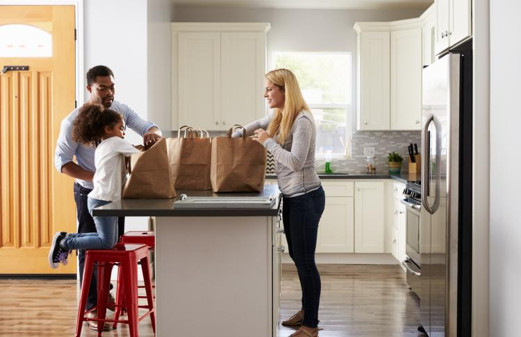 a family is shown in the kitchen after grocery shopping
