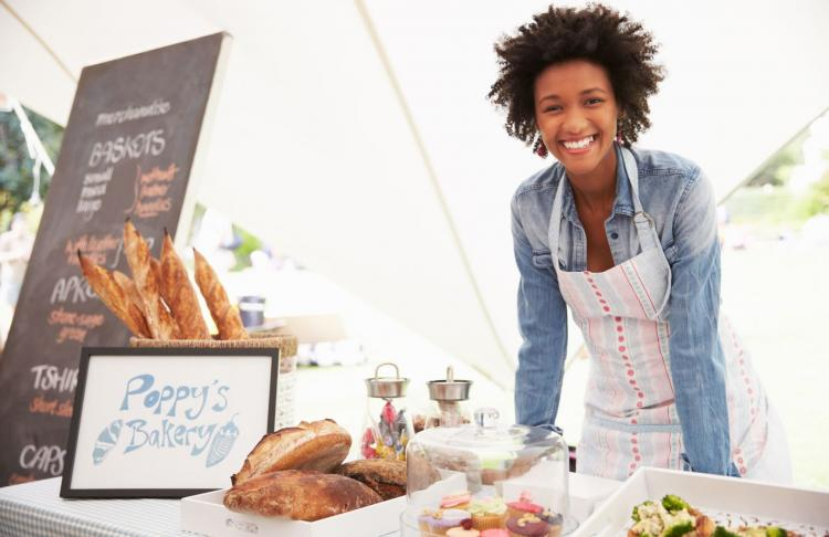 a small business owner smiles into the camera while serving at a farmers market