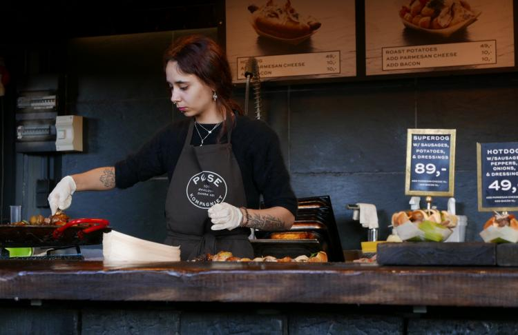 A woman is working in the kitchen at a restaurant