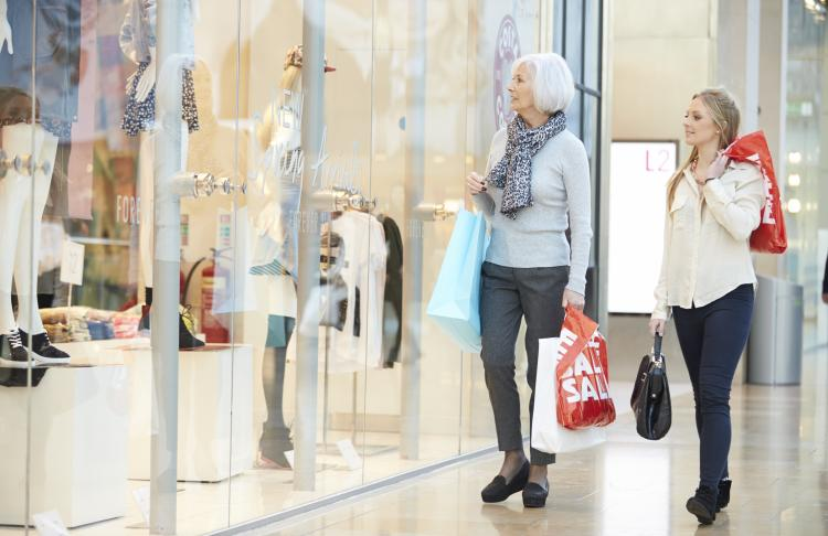 Older and young woman at mall holding shopping bags