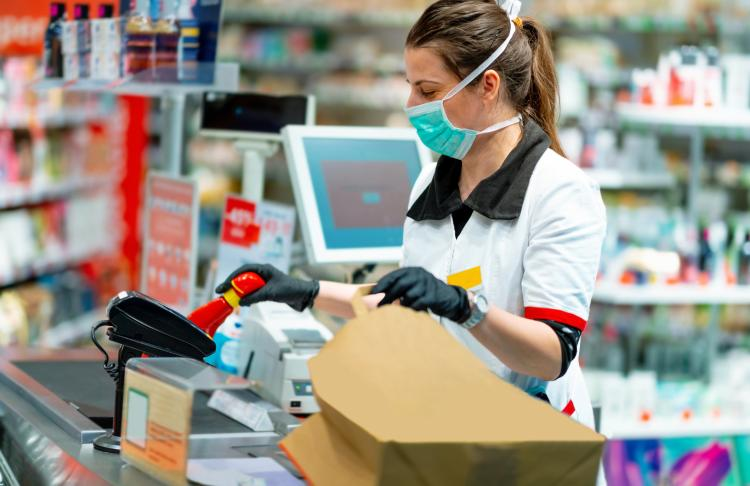 A supermarket clerk rings up groceries wearing gloves and a mask